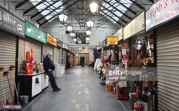 Man waits for customers outside his market stall in Leek Market on November 11, 2020 in Leek, England. The Booksellers Association has called on the...