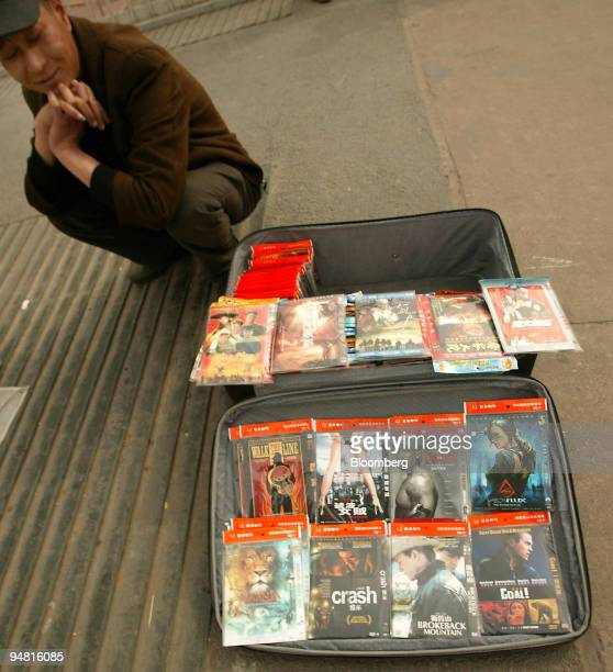 A man waits for customers to buy his pirated DVDs featuring Oscar winning movies like 'Walk the Line' 'Brokeback Mountain' and 'Crash' each selling...