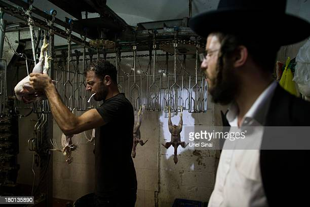 A man waits for his chickens to come out of a cleaning machine in a slaughterhouse as UltraOrthodox Jews perform the Kaparot ceremony on September 9...