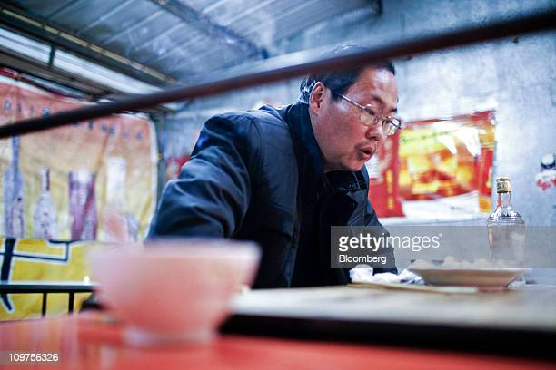 A man waits for his dumplings to cool at a night market in Chuzhou Anhui Province China on Wednesday March 2 2011 As Chinese Premier Wen Jiabao this...