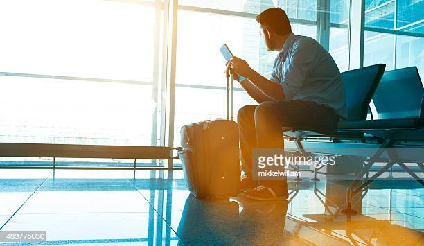 Man waits for plane at airport and looks for flight