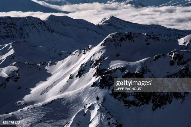 TOPSHOT A man waits for skiers on March 10 2017 in Beaufort during the third stage of the 32nd edition of ski mountaineering competition Pierra Menta...