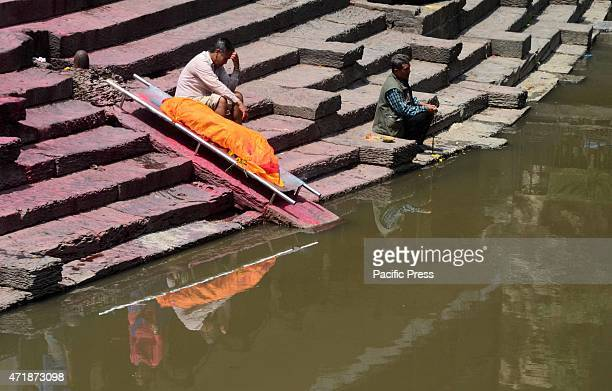 A man waits for the cremation of a family member who died in the earthquake at Pashupatinath Kathmandu in Nepal
