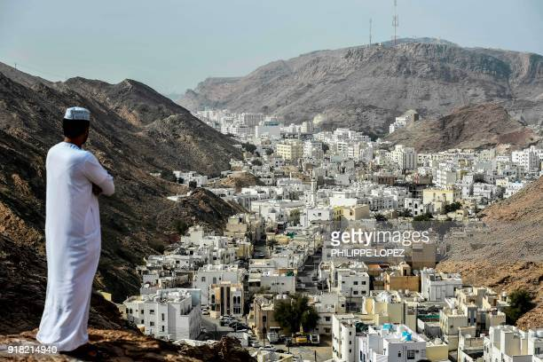 TOPSHOT A man waits for the peloton as it arrives in a street of alWadi alKabir during the second stage of the 2018 cycling Tour of Oman from Sultan...