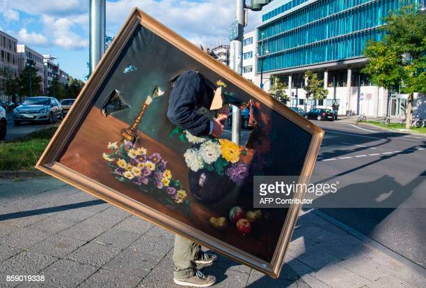 A man waits for the traffic light to change as he carries a weathered reproduction painting in Berlin on October 8 2017 / AFP PHOTO / John MACDOUGALL