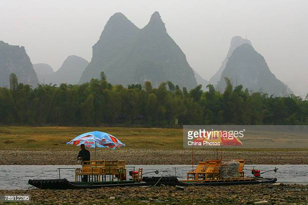 A man waits for tourists on a raft on the dry riverbed of Lijiang River on January 12 2007 in Guilin of Guangxi Zhuang Autonomous Region southern...