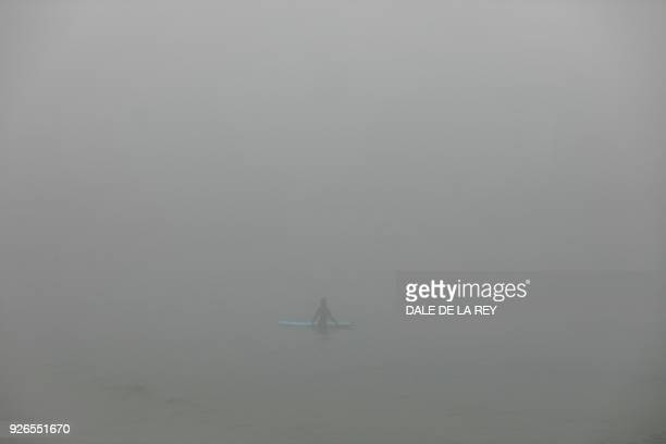 TOPSHOT A man waits for waves while surfing on a foggy morning at a beach in Hong Kong on March 3 2018 / AFP PHOTO / Dale DE LA REY