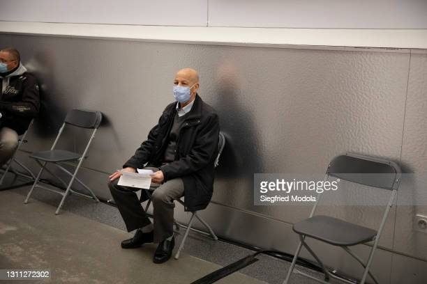 Man waits his turn to be vaccinated inside the Paris Stade de France following its conversion into a Covid-19 vaccination centre on April 7, 2021 in...