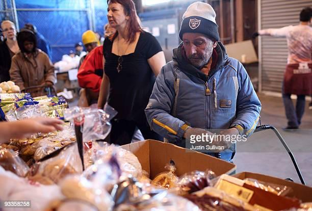 A man waits in line to receive food for a Thanksgiving meal November 24 2009 at the Alameda Food Bank in Alameda California Hundreds of needy people...