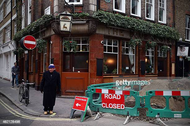 A man waits next to roadworks outside The Blue Post pub in Soho on January 21 2015 in London England A growing number of campaigners including...