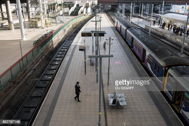 A man waits on a platform in Manchester Victoria train station during a reduced transport service due to industrial action taken by the RMT union in...
