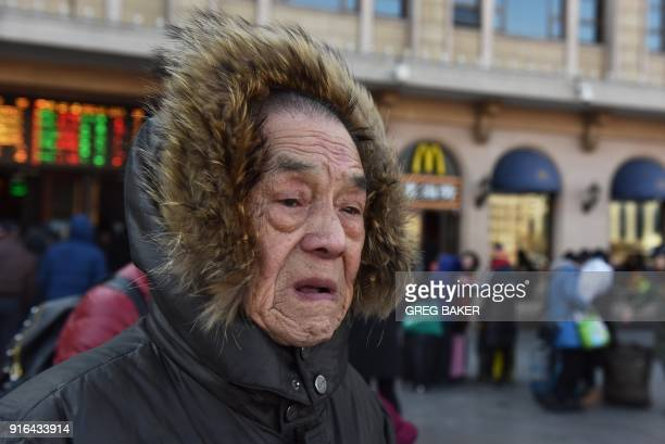 A man waits outside a railway station in Beijing on February 10 as travellers depart the capital ahead of the Lunar New Year China is in the midst of...