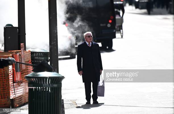 A man waits to cross a street in Manhattan on March 14 2020 in New York City The World Health Organization said March 13 2020 it was not yet possible...