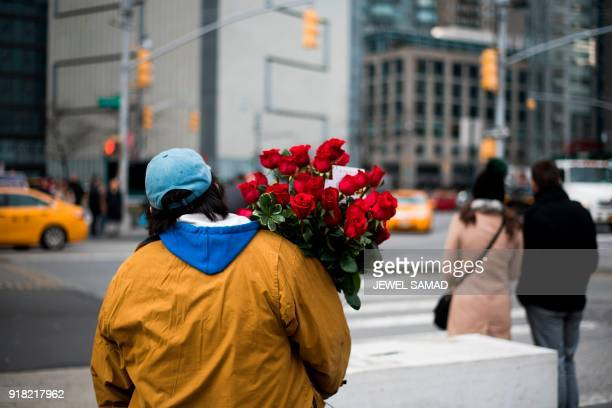 A man waits to cross a street with a bunch of red roses during Valentine's Day in New York on February 14 2018 / AFP PHOTO / Jewel SAMAD