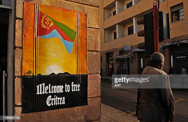 Man waits to cross the road beside a patriotic poster in Asmara, Eritrea, on July 18, 2013. Long criticised for backing rebel groups across the Horn...