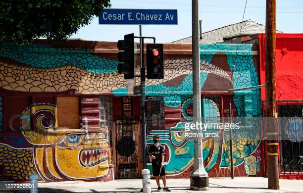 Man waits to cross the street in the largely Latino neighborhood of East Los Angeles, August 7, 2020 in Los Angeles, California during the...