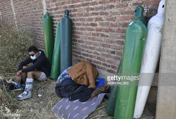 Man waits to refill an empty oxygen tank outside Valle Alto Medical Oxygen plant in Arbieto municipality, 50 km from Cochabamba, on May 27, 2021.