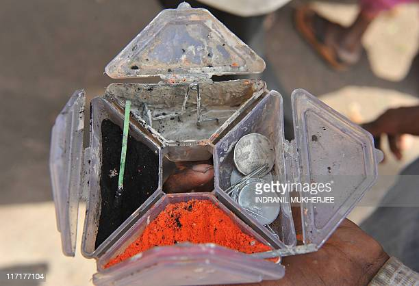 A man waits with a container holding powder used to place tilak on the forehead of VarkariHindu pilgrims in exchange for a few rupees during the...