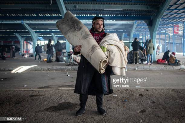 Man waits with his belongins at a makeshift camp for refugees and migrants in an empty market hall on March 05, 2020 in Edirne, Turkey. Thousands of...