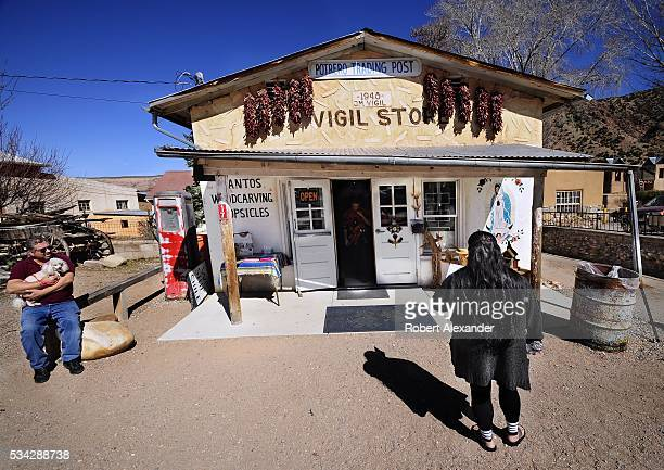 A man waits with his pet poodle dog outside the Potrero Trading Post in Chimayo New Mexico on February 27 2016 The smalll store is next to the...