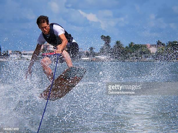 Man Wakeboarding Jump Kicks Up Water Spray