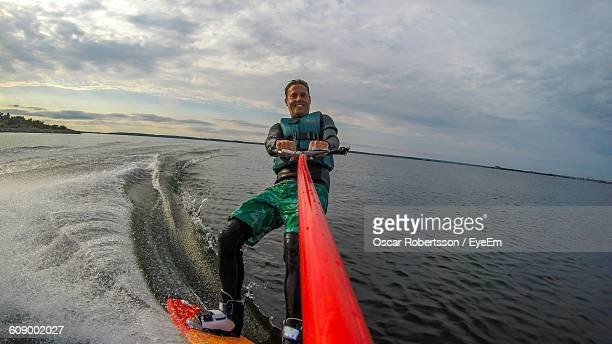 man wakeboarding on sea against cloudy sky - waterskiing stock photos and pictures