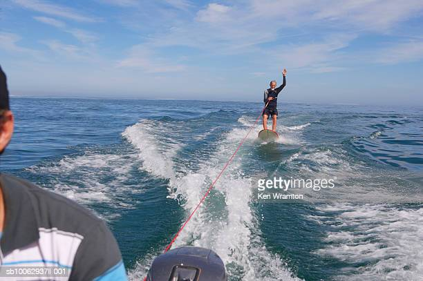 man wakeboarding, view from boat - waterskiing stock photos and pictures