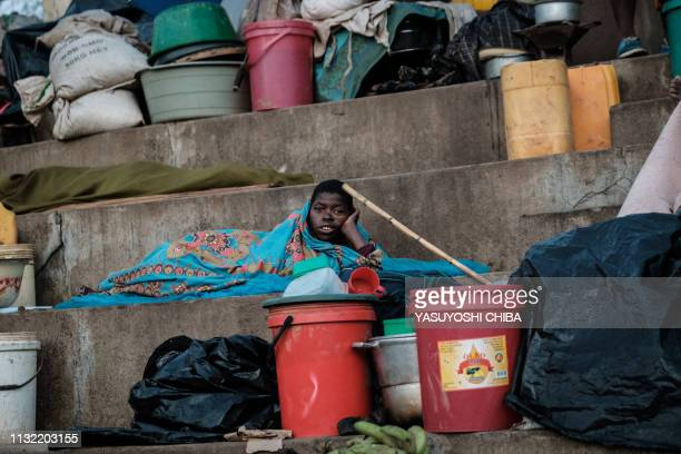 A man wakes up in the morning as he stays in shelter at the stands of Ring ground in Buzi Mozambique on March 23 2019 The death toll in Mozambique on...