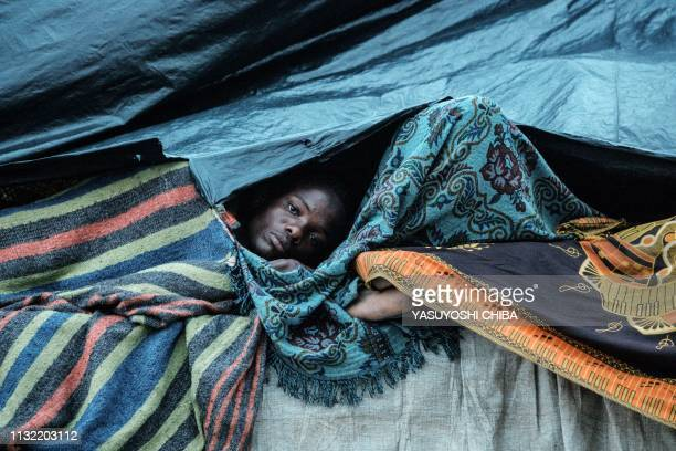 A man wakes up under plastic sheets as he stays in shelter at the stands of Ring ground in Buzi Mozambique on March 23 2019 The death toll in...
