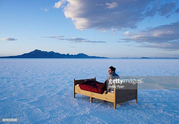 man waking in bed in salt flats. - onirico foto e immagini stock