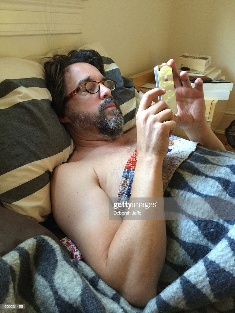 Man waking up checking iPhone in bed