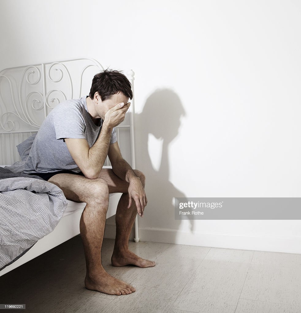 man waking up in his bedroom while sitting at bed : Stock Photo