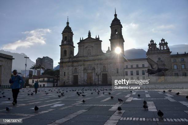 Man walk by a near empty Plaza de Bolivar during a total lockdown amid the second wave of the Coronavirus pandemic on January 16, 2021 in Bogota,...