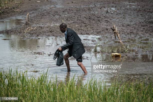 A man walk in a flooded area after the road was destroyed by the cyclone Idai in John Segredo on March 24 2019 Cyclone Idai smashed into Mozambique's...