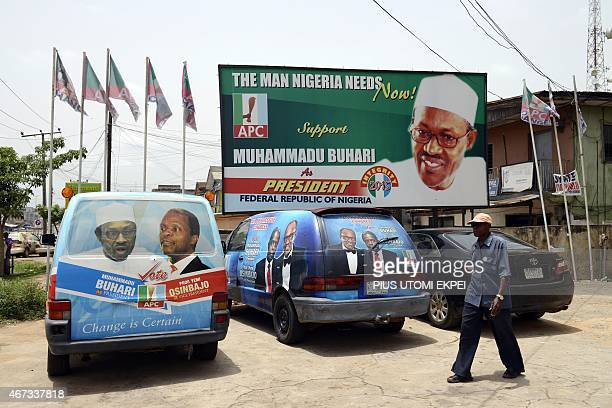 A man walk past a billboard and branded campaign vehicles of the main opposition All Progressives Congress presidential candidate Mohammadu Buhari...