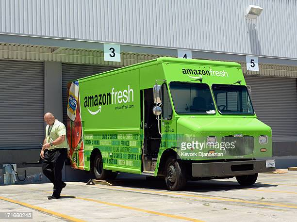 A man walk past an Amazon Fresh truck parked at a warehouse on June 27 2013 in Inglewood California Amazon began groceries and fresh produce delivery...