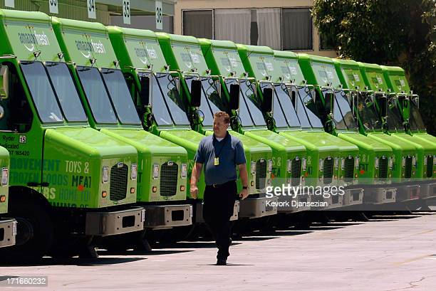 A man walk past an Amazon Fresh trucks parked at a warehouse on June 27 2013 in Inglewood California Amazon began groceries and fresh produce...