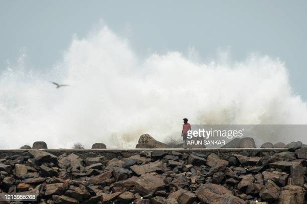 A man walk past as waves hit a breakwater at Kasimedu fishing harbour in Chennai on May 19 as Cyclone Amphan barrels towards India's eastern coast...