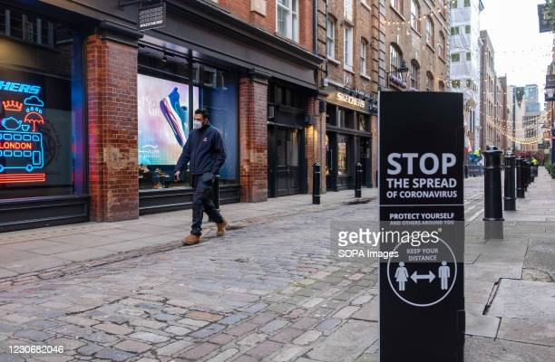 Man walk past closed shops and COVID-19 social distancing sign at Covent Garden, a shopping and entertainment hub in west end London. UK has...