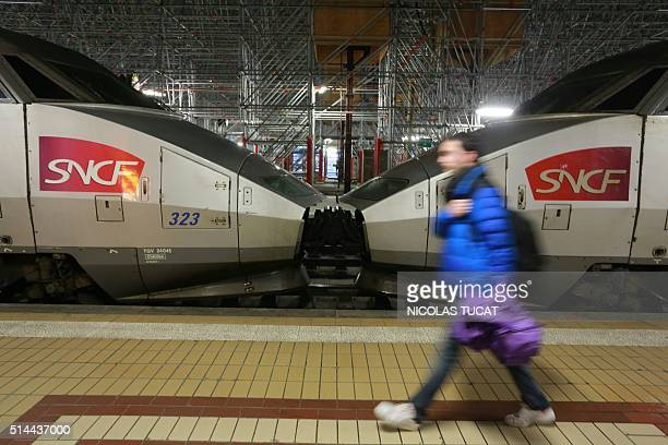 A man walk past highspeed TGV trains at the Bordeaux train station on March 9 2016 France was bracing for a wave of protests today against deeply...