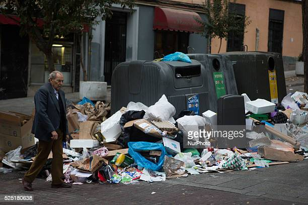 A man walk past piles of rubbish dumped around recycle containers during the fourth day of a garbage collectors strike in Madrid Spain Street...