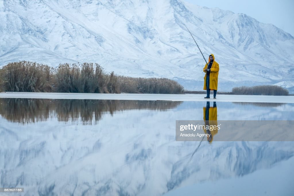 A Man walk try to catch fishes on a frozen lake as it is zero celcius degree in Van, Turkey on November 30, 2017.