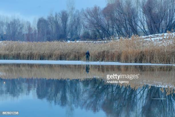 Man walk try to catch fishes on a frozen lake as it is zero celcius degree in Van Turkey on November 30 2017