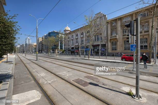 a man walking across a cable car track during quarantine days in izmir. - emreturanphoto stock pictures, royalty-free photos & images