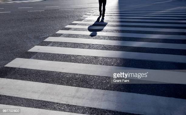 man walking across large intersection. - oversteken stockfoto's en -beelden