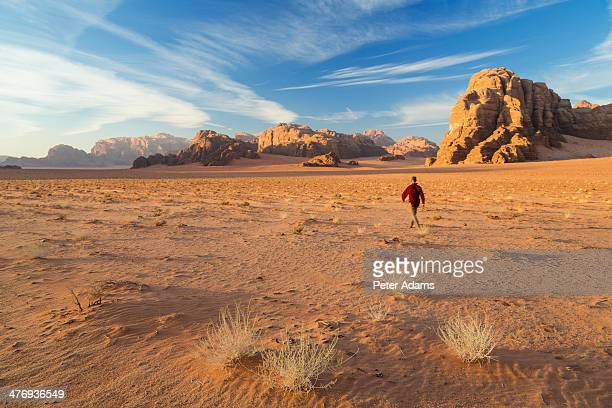 Man walking across the desert, Wadi Rum, Jordan
