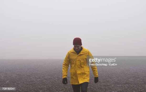 man walking against clear sky - raincoat stock photos and pictures
