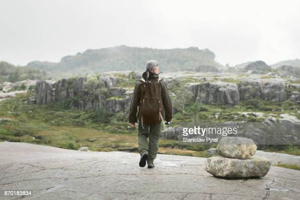 Man walking alone in mountains, rocks around, rainy weather