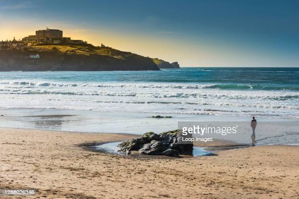 Man walking alone in the evening light on Great Western Beach in Newquay in Cornwall.