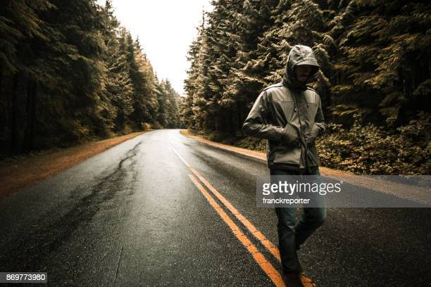 man walking alone in the road - parka coat stock photos and pictures
